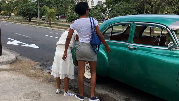 Dos mujeres abordan un taxi colectivo (almendrón) en La Habana. (14ymedio)