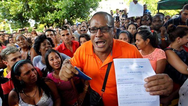 Un hombre, con un pasaporte en su mano y algunos documentos que confirman sus planes de viaje, protesta ante la embajada de Ecuador. (Foto EFE)