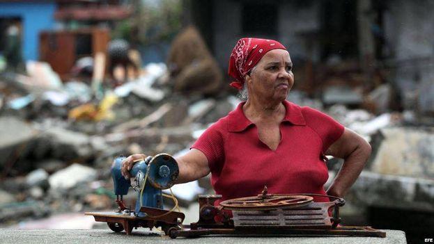 Una mujer recoge algunas pertenencias entre la destrucción dejada por Matthew en Baracoa. (EFE)
