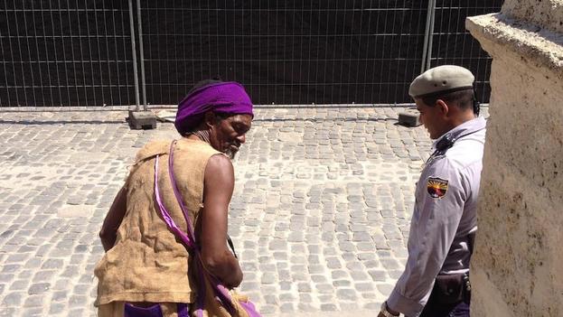 Un agente de policía echa a un mendigo de la Plaza de la Catedral. (La Habana)