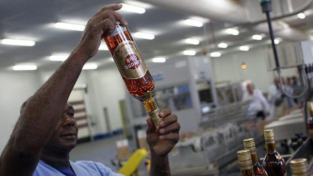 Un operario revisa una botella de la línea de producción en la fábrica de ron Havana Club. (EFE/Alejandro Ernesto)