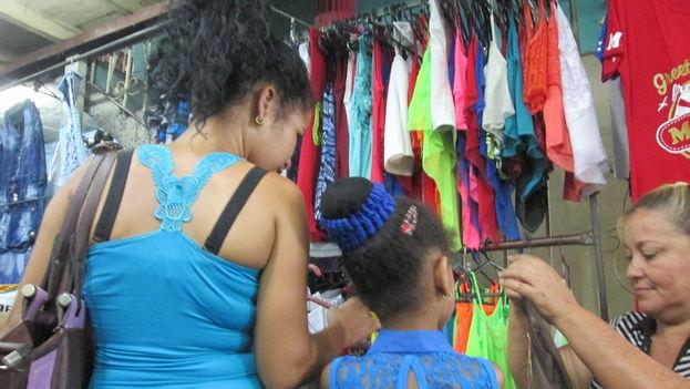 Una mujer vende ropa en el local rentado Pais Viena de la Calle Monte. (14ymedio)