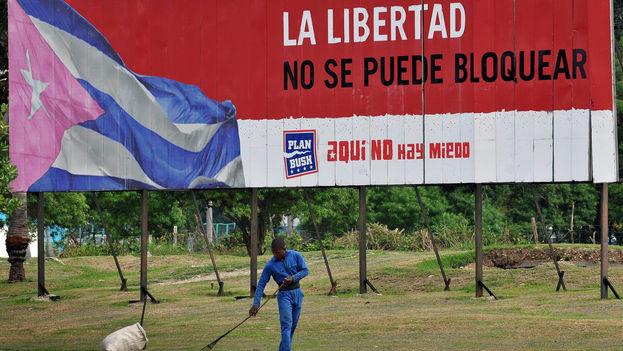 Un trabajador barre frente a un anuncio propagandístico en La Habana. (EFE)