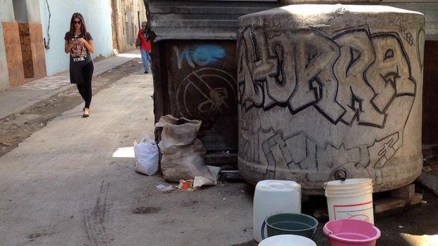 Los vecinos colocan en fila sus cubos y otros envases a la espera de que llegue el suministro de agua, La Habana. (14ymedio)