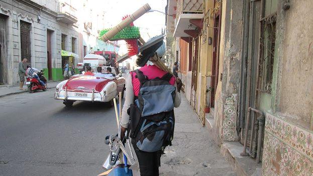 Un vendedor de escobas y otros utensilios de limpieza ofrece su mercancía en una calle de La Habana. (14ymedio)