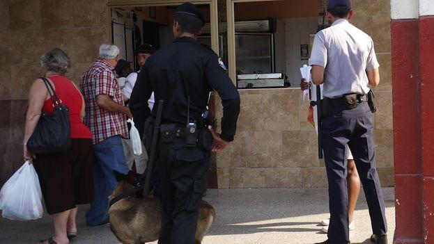 Un policía comprueba los papeles y la mercancía de una vendedora ambulante (Foto Reinaldo Escobar/14ymedio)