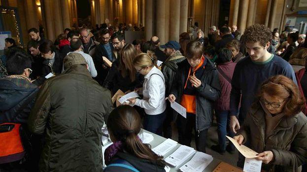 Los ciudadanos escogen las papeletas para ejercer su voto en las elecciones en el colegio electoral situado en la Universitat de Barcelona. (EFE/Toni Albir)
