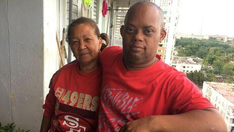Alain Gómez Acuña junto a su madre en el edificio donde viven en el municipio Plaza de la Revolución. (14ymedio)
