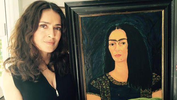 La actriz mexicana Salma Hayek posa junto a un cuadro pintado por ella misma de Frida Kahlo, a quien interpretó bajo las órdenes de Weinstein como productor. (@salmahayek)