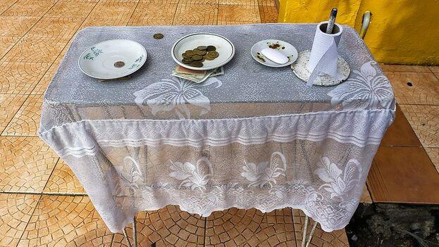 A las afueras de un baño en una cafetería estatal, una mesa con monedas reclama las propinas a cambio de un trozo de papel sanitario. (E. Pighetti)