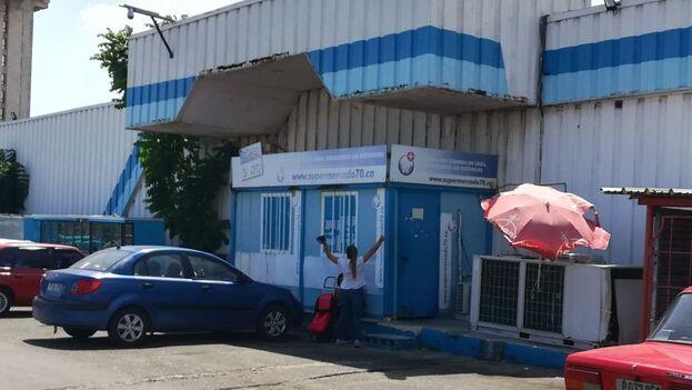 En un contenedor climatizado, a pocos metros de la larga cola para entrar al mercado de 3ra y 70 en La Habana, despachan la mercancía comprada 'online'. (14ymedio)