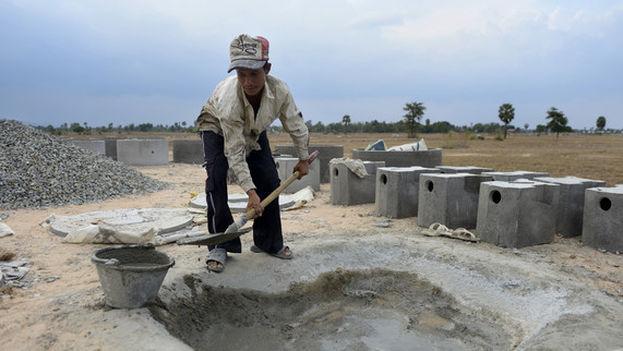Un hombre mezclando cemento para producir piezas para retretes. (EFE)