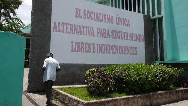 Un hombre pasea al lado de un eslogan socialista. (14YMEDIO)