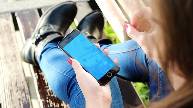 Una joven consulta su teléfono móvil. (CC)